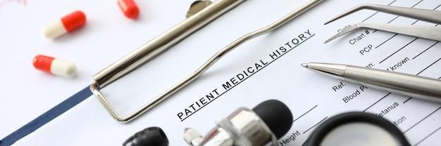 Medizinische geräte und pillen, die in der nahaufnahme der patientenanamnese liegen