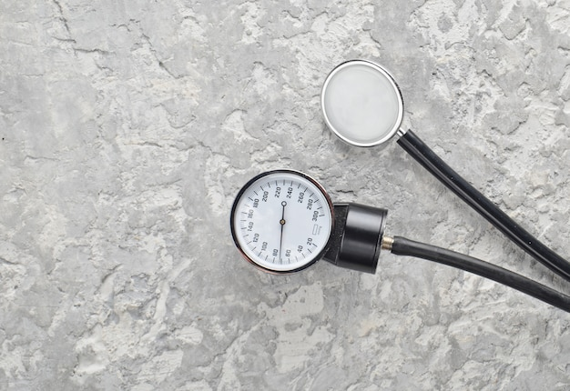 Medizinische geräte zur druck- und stethoskopmessung auf einem betontisch. draufsicht.