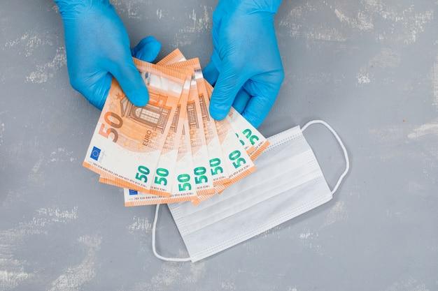 Medizinische gesichtsmaske auf gips tisch und hände, die banknoten halten.