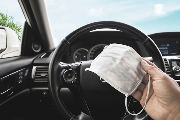 Medizinische gesichtsmaske, die auf fahrerhand innen zum auto hält