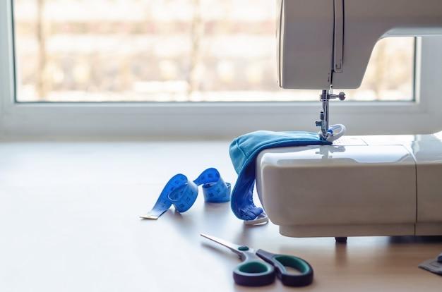 Medizinische gesichtsmaske nähen. zuhause arbeiten. herstellung persönlicher schutzausrüstung bei krankheit, epidemie, quarantäne. coronavirus-konzept. speicherplatz kopieren