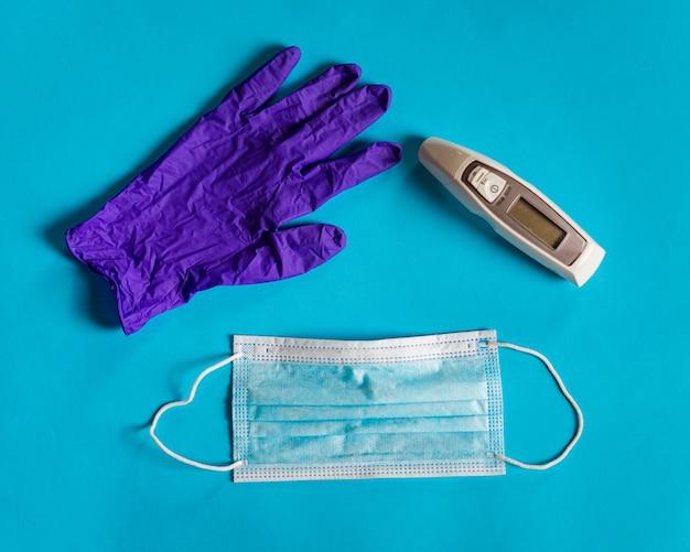 Medizinische gesichtsmaske, thermometer und handschuh auf blauem hintergrund. coronavirus schutz.