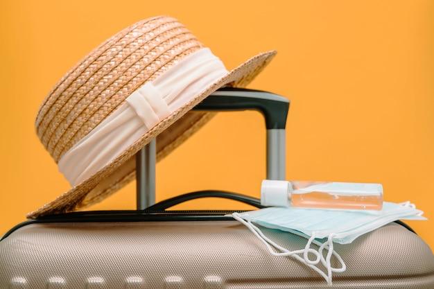 Medizinische gesichtsmasken und händedesinfektionsmittel befinden sich auf dem reisegepäckkoffer. reisekonzept