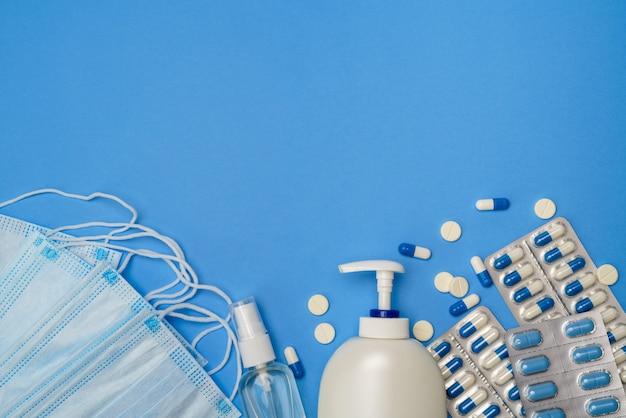 Medizinische gesichtsschutzmasken, händedesinfektionsgel und spay für hygiene und pillen auf blauem tisch