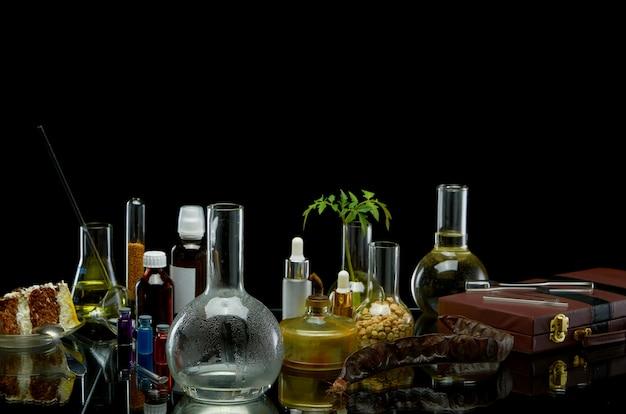 Medizinische gläser mit reagenzien und eine pflanze mit einem lederkoffer