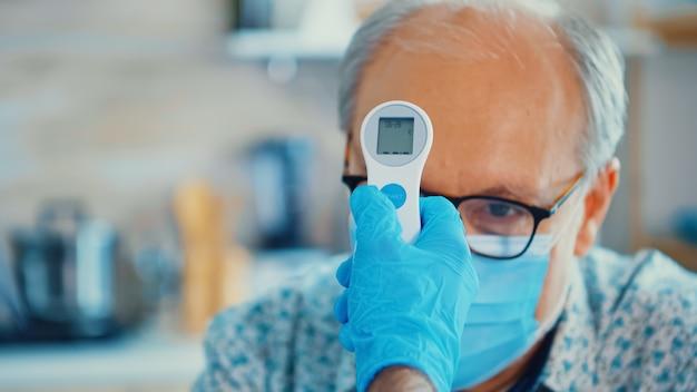 Medizinische hilfe, die die körpertemperatur des älteren mannes mit infrarot-thermometer in der küche überprüft. sozialarbeiter, die schutzbedürftige personen überprüfen, um die verbreitung von krankheiten zu verhindern
