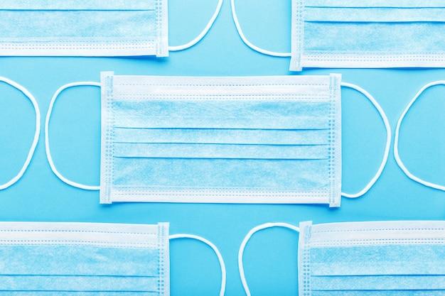 Medizinische hygienemaske, gesichtsschutzmasken auf blauem hintergrund. einweg-gesichtsmaske zum schutz vor coronavirus covid-19, verschmutzung, virus, grippe.
