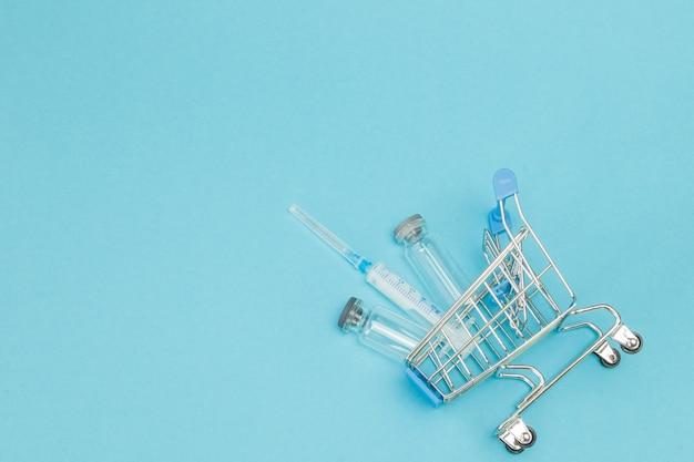 Medizinische injektion im einkaufswagen auf blau.