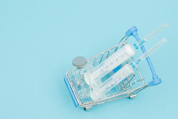 Medizinische injektion im einkaufswagen auf blauem hintergrund. kreative idee für das geschäftskonzept von gesundheitskosten, drogerie, krankenversicherung und pharmaunternehmen