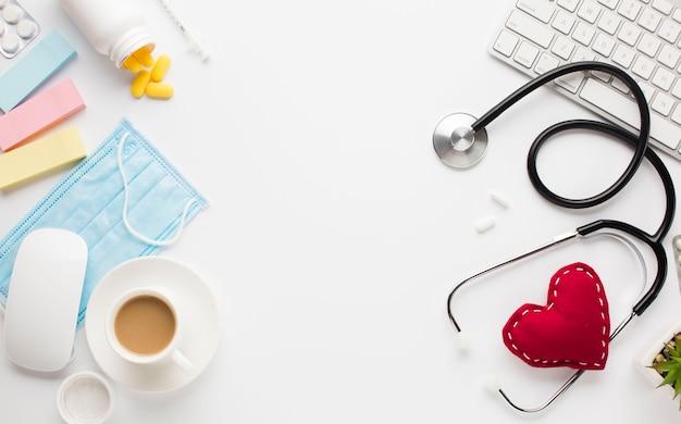Medizinische instrumente mit pillen nähern sich stoffherzen und drahtloser ausrüstung über weißer oberfläche