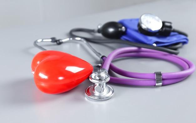 Medizinische instrumente und rotes herz für hno-arzt auf weißem tisch