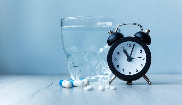 Medizinische kapselpillen, glaswasser und wecker auf blauem hintergrund. konzept gesundheit