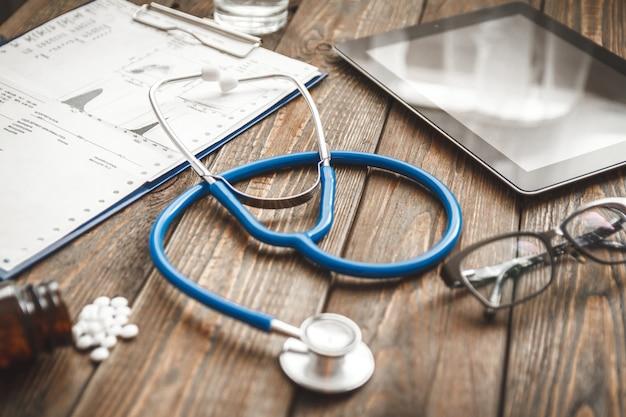 Medizinische karte des patienten, stethoskop, tablette auf holztisch