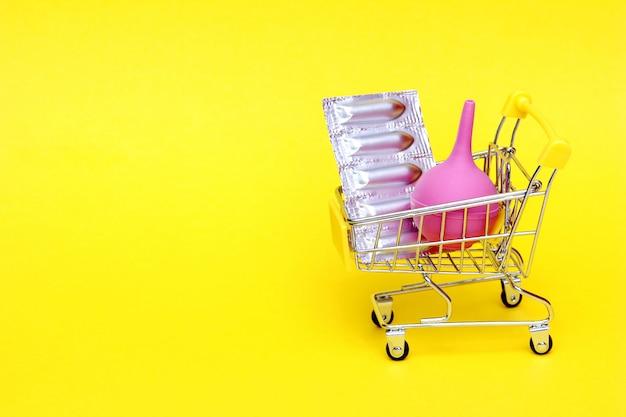 Medizinische kerzen in einer silbernen blisterpackung und ein medizinischer einlauf aus rosa gummi werden in einen spielzeug-einkaufswagen gelegt. verpackung von verhütungsmitteln, vaginal- und rektalkerzen. einlauf in der medizin.