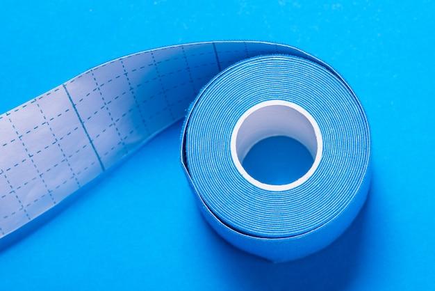 Medizinische kinesiologie-bandrolle auf blauer oberfläche, nahaufnahme