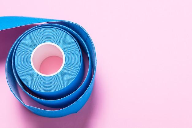 Medizinische kinesiologie-bandrolle auf rosa hintergrund, nahaufnahme