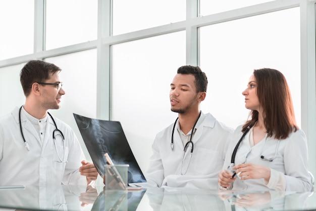 Medizinische kollegen diskutieren röntgen, sitzen am bürotisch. das konzept der gesundheit