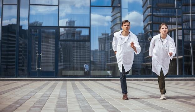 Medizinische kollegen laufen eine stadtstraße hinunter zu einem notruf. foto mit einem exemplarplatz.