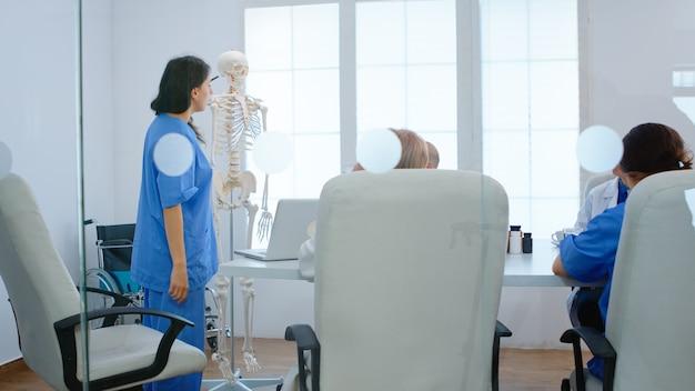 Medizinische krankenschwester, die auf die halswirbelsäule des anatomischen modells des menschlichen skeletts zeigt und den mitarbeitern medizinische verfahren im besprechungsraum des krankenhauses erklärt. ärzte diskutieren über krankheitssymptome