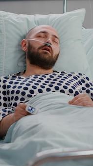 Medizinische krankenschwester, die das krankheitssymptom der temperaturüberwachung während des erholungstermins im krankenhaus überprüft ...