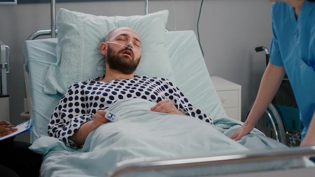 Medizinische krankenschwester, die das krankheitssymptom der temperaturüberwachung während des genesungstermins in der krankenstation überprüft. kranker patient, der im bett ruht, während der assistent die rehabilitationsexpertise analysiert