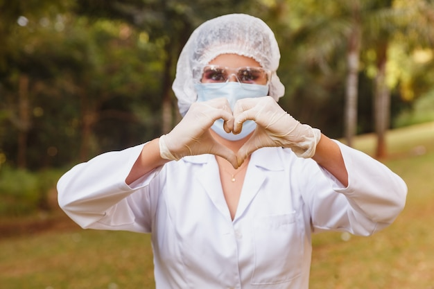 Medizinische krankenschwester, die herz mit hand macht, chirurgische maske tragend