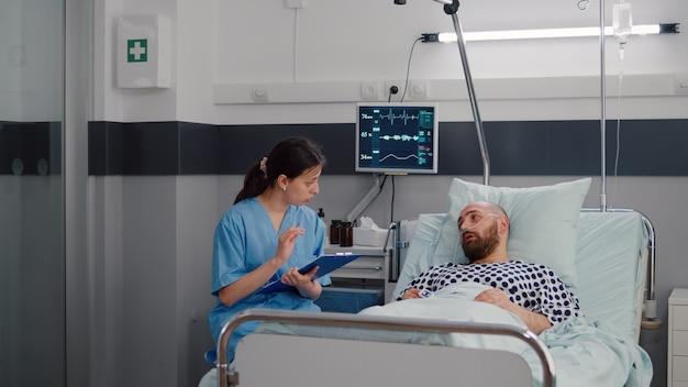 Medizinische krankenschwester, die krankheitsbehandlung mit hospitalisiertem kranken mann bespricht