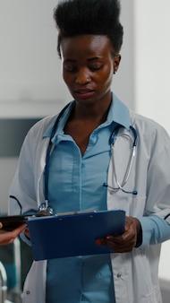 Medizinische krankenschwester, die medizinische expertise mit tablet-computer für eine spezialisierte schwarze ärztin zeigt