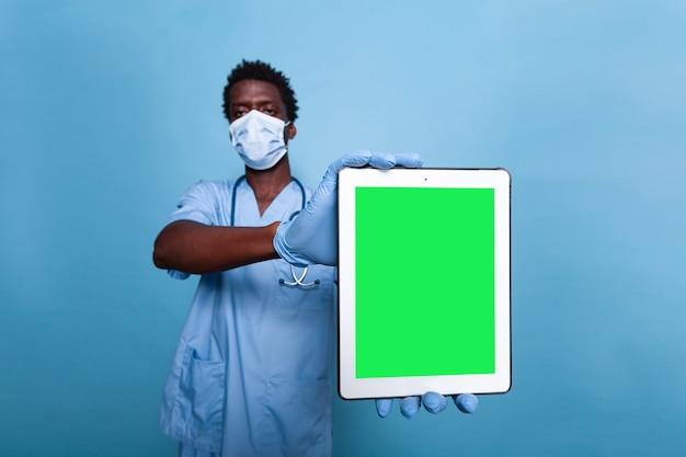 Medizinische krankenschwester, die vertikalen grünen bildschirm auf tablet hält