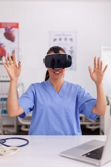 Medizinische krankenschwester, die virtuelle realität mit vr-brille im krankenhausbüro erlebt. therapeut, der medizinische innovationsausrüstungsgerätebrille verwendet, medizin, arzt, gesundheitswesen, beruflich, zukunft, visi