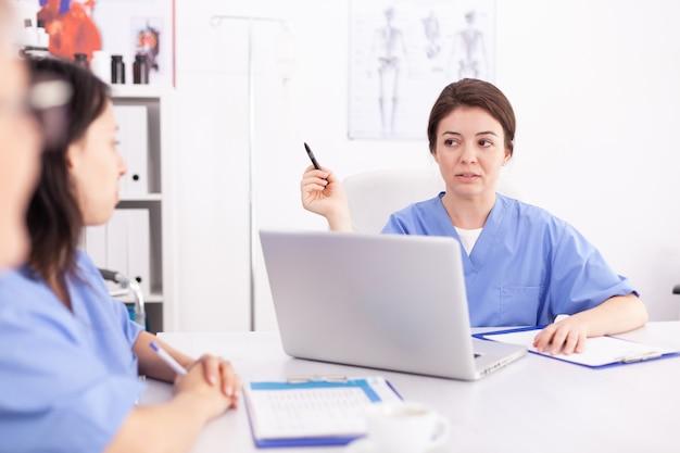 Medizinische krankenschwester mit laptop während des briefings mit medizinexperten im konferenzraum des krankenhauses. kliniktherapeut mit kollegen, die über krankheit, experten, spezialisten, kommunikation sprechen.