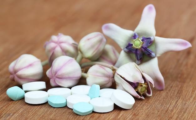Medizinische kronenblume mit tabletten auf holzoberfläche