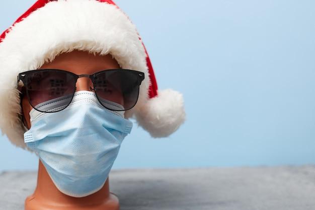 Medizinische maske auf einem mannequin und einem neujahrshut weihnachten 2021 auf einem blauen hintergrund