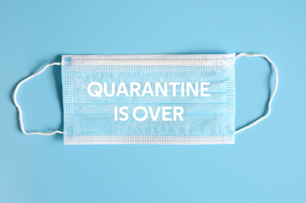 Medizinische maske blaue farbe zum schutz vor bakterien auf blauem hintergrund und textquarantäne ist über ofl schriftart