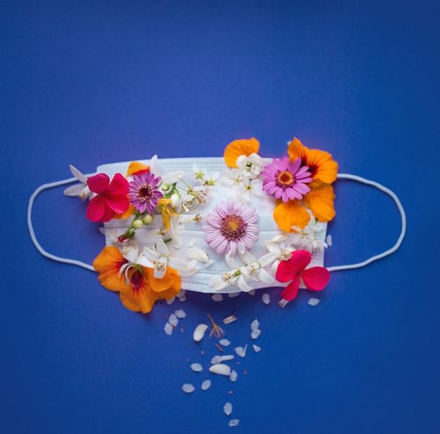Medizinische maske blüht oben mit verschiedenen farbblumen auf rosa lila hintergrund draufsicht mit. coronavirus-quarantänekonzept