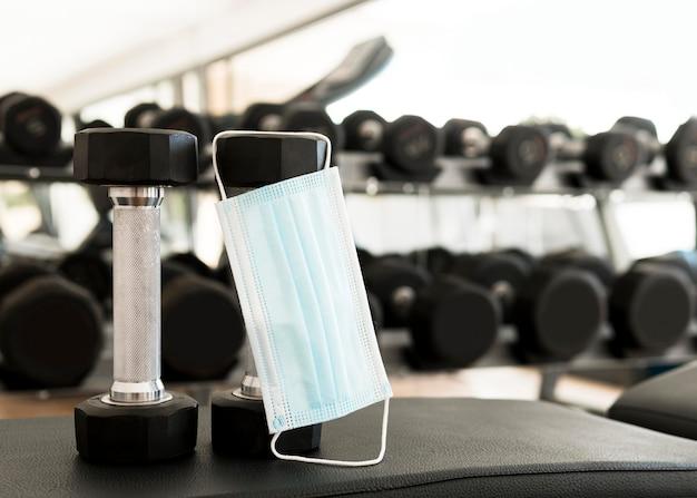 Medizinische maske, die von den gewichten im fitnessstudio hängt
