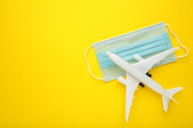Medizinische maske gegen coronavirus mit flugzeug auf gelber wand. reisekonzept. draufsicht