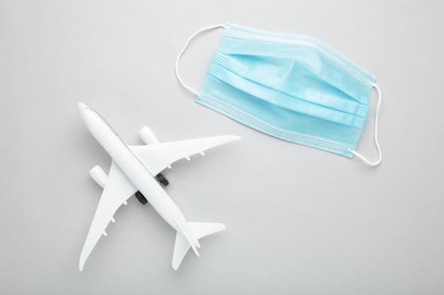 Medizinische maske gegen coronavirus mit flugzeug auf grauer wand. reisekonzept. draufsicht