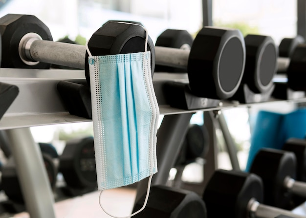 Medizinische maske im fitnessstudio, die an gewichten hängt