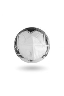 Medizinische maske ist auf einem fußball auf weißem tisch gekleidet. einschränkungen bei sportveranstaltungen
