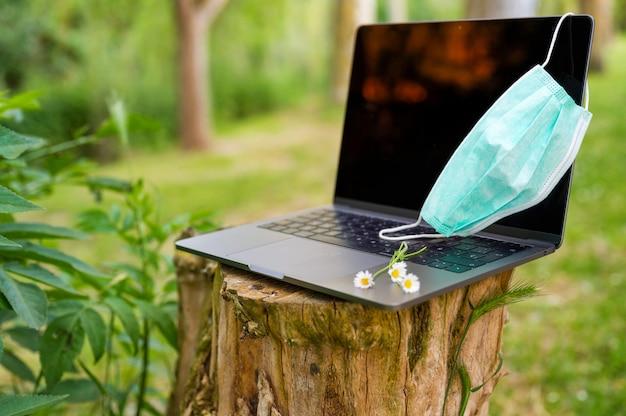 Medizinische maske, laptop, auf einem baumstamm im freien