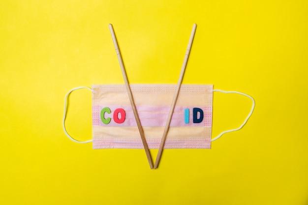 Medizinische maske mit der aufschrift covid19 auf gelbem hintergrund und asiatischen essstäbchen