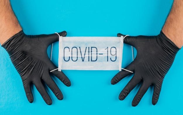 Medizinische maske mit text covid-19 in einer hand mit schwarzen handschuhen draufsicht
