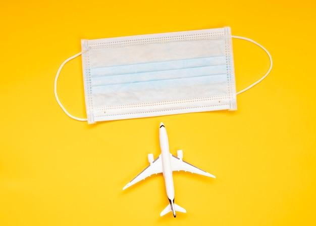 Medizinische maske, reisen, flugzeuge, gelber hintergrund, probleme beim reisen mit covid-19