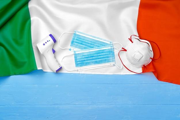 Medizinische maske und berührungsloses thermometer auf flagge von italien auf blauer holzoberfläche