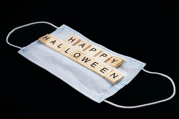 Medizinische maske und hölzerne wörter happy halloween auf schwarz Premium Fotos