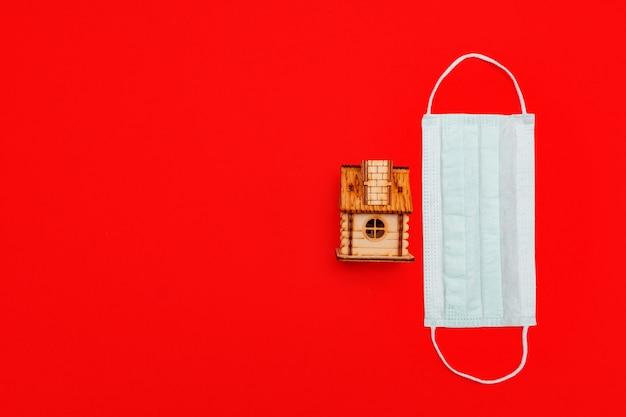 Medizinische maske und hölzernes spielzeughaus auf rotem hintergrund. konzept der selbstquarantäne zu hause als vorbeugende maßnahme gegen virusausbruch.