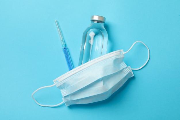 Medizinische maske und medikamente auf blau
