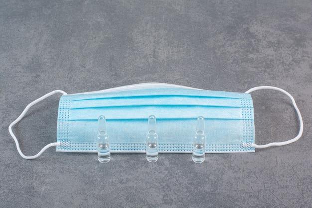 Medizinische maske zum schutz gegen coronavirus mit ampullen.