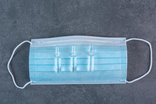 Medizinische maske zum schutz vor koronaviren mit ampullen Kostenlose Fotos